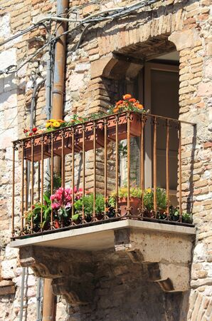 Medieval balcony with pots and flowers photo
