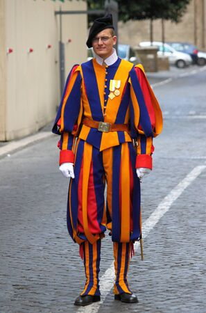 VATICAN CITY, ITALY - APRIL 22: A Papal Swiss Guard stands guard at the entrance of Saint Peters Basilica on April 22, 2012. Swiss Guards in their traditional uniform.