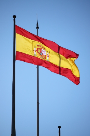 waft: Spanish red, yellow and red flag fluttering in the breeze Stock Photo