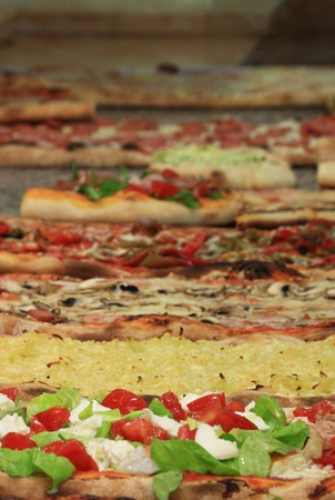 Different varieties of pizza displayed in a Pizzeria photo