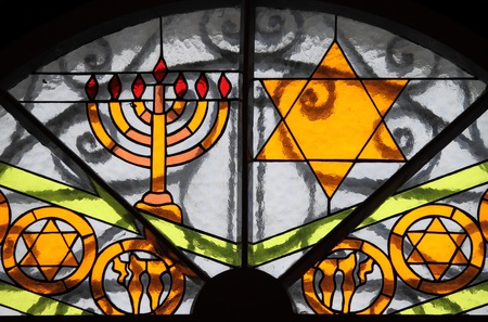 Magen David star and Menorah painted on a a stained glass window photo