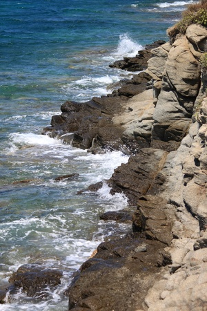 Waves from the ocean hitting against a rock cliff photo