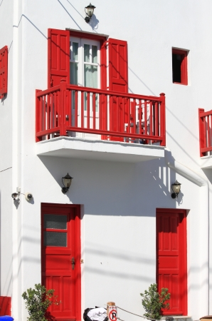 Beautiful white house with red colored windows and doors in Mykonos island, Greece photo