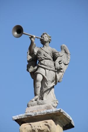 Statue of angel playing the horn, symbol of the power of god photo