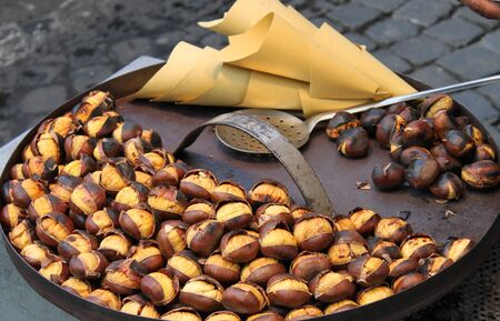 Grilled chestnuts for sale in a market stall Archivio Fotografico