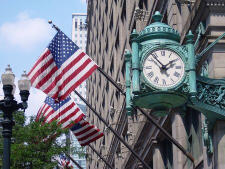 street corner: Marshall Fields clock over american flags on State Street in Chicago, USA Stock Photo