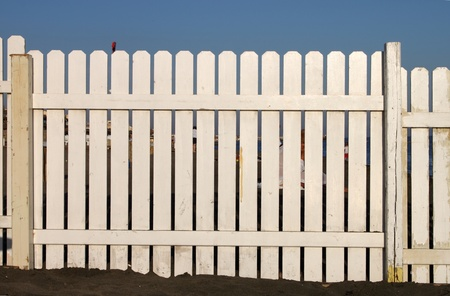 A wooden white fence on the beach on a blue sky background photo