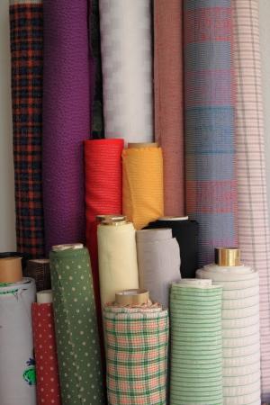 Rotoli di tessuto colorato in vendita in una merceria Archivio Fotografico - 16080531