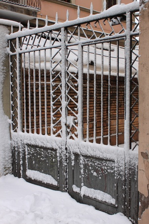 Iron gate covered by snow in wintertime photo