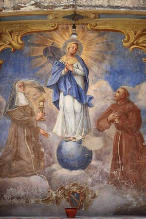 Assisi, Italy - April 28, 2012: Ancient fresco of the Virgin Mary with St. Francis of Assisi and St. Rita of Cascia