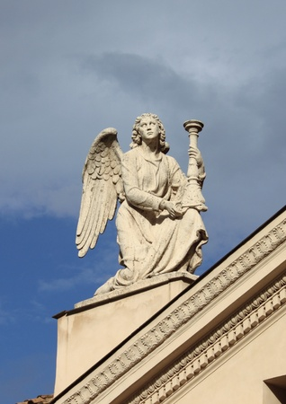 Angel statue with candelabra on top of Saint Rocco church in Rome, Italy photo