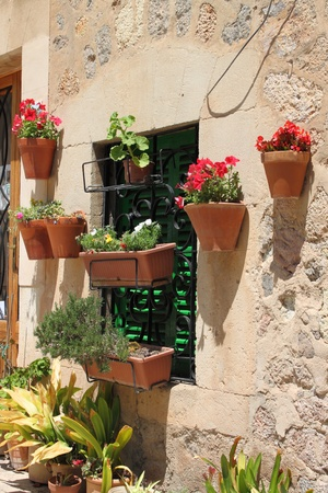 Valldemossa, Spain - April 28, 2012: Red bricks wall of a house with window and flower pots