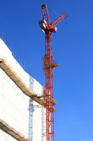 Red crane by the construction site of a skyscraper photo