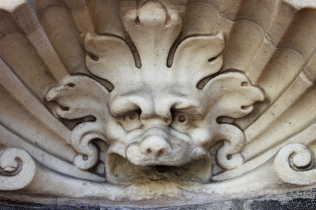 spitting: Baroque wall fountain with satyr spitting water