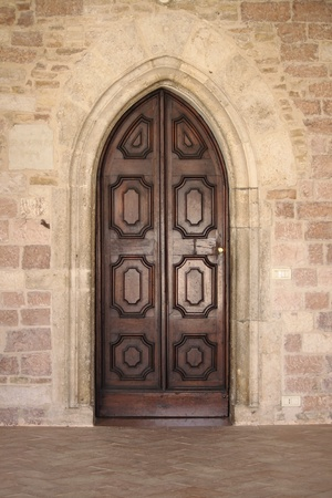 Medieval front door in Assisi, Italy photo
