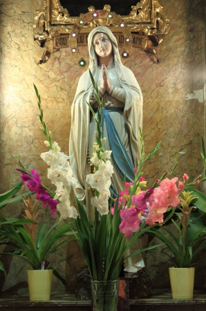 Virgin mary statue with flowers in niche
