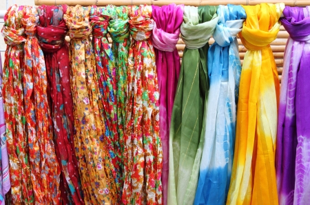 bufandas: Pa?os de colores que cuelgan en un estante de una tienda de moda