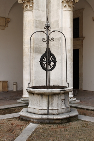 urbino: Urbino, Italy - March 17, 2013: Medieval water well in a cloister Editorial