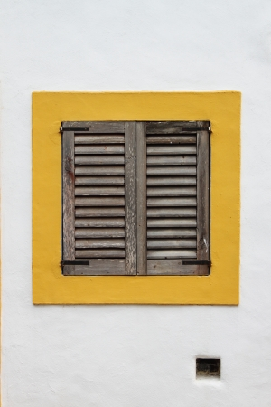 baffle: Brown window shutters on a yellow and white wall background
