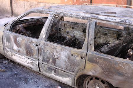 blazed: Burned car in a parking lot