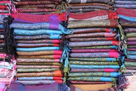 sciarpe: Pile di sciarpe pashmina per la vendita in un negozio di moda