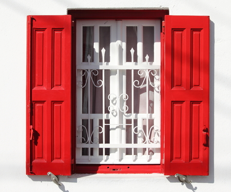 grille: Beautiful window with grille and red shutters in Greece Stock Photo