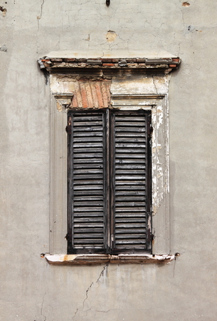 baffle: Brown window shutters on a old white wall Stock Photo