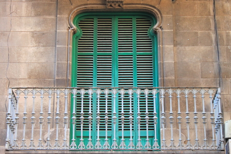 balcony window: Arched window with closed shutters and balcony