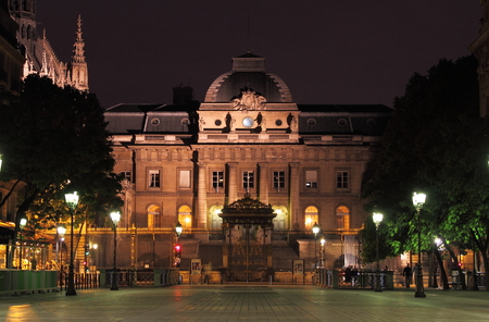 Palace of justice by night in Paris, France Редакционное