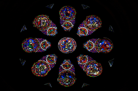 Stained glass rose window with catholic scenes