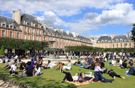 PARIS, FRANCE - MAY 24, 2015: People relaxing on green lawns of the famous Place des Vosges - the oldest planned square in Paris located in Marais district on May 24, 2015 in Paris