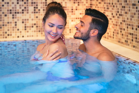 Happy young couple doing a swimming pool spa center day - Romantic lovers having a tender moment on vacation in resort wellness hotel - Relationship, recreation, relaxation and love concept Archivio Fotografico