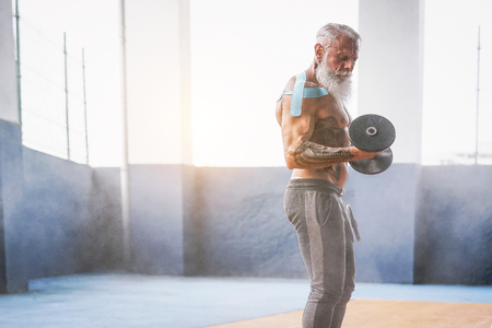 Fitness beard man doing biceps curl exercise  inside a gym - Tattoo senior man training with dumbbells in wellness club center - Body building and sport fit concept Foto de archivo