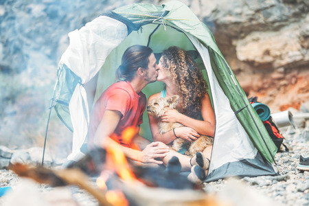 Travel couple kissing while sitting in the tent with their pet - Happy man and woan having a romantic moment vacation camping around rock mountain next to the fire - Love, travel, holidays concept 写真素材