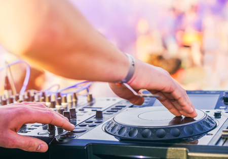 Dj mixing at beach party festival with people dancing in the background - Deejay playing music mixer audio outdoor - Concept of summer events and club outdoor 免版税图像 - 119152263