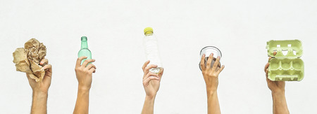 Human hands holding recyclable objects as paper, glass, plastic, aluminium on a white background - Eco concept with recycling - Focus on hands 免版税图像 - 119152265