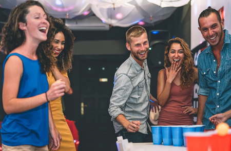 Happy friends playing beer pong in a cocktail bar - Young millennials people having fun doing party alcohol games at night pub - Friendship and youth lifestyle nightlife concept