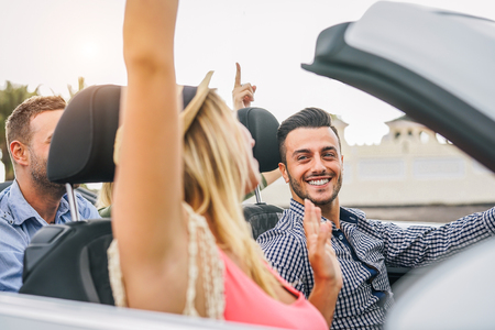 Happy friends having fun in convertible car at sunset in vacation - Young rich people making party and dancing in auto cabriolet during their road trip - Friendship, travel, youth lifestyle concept