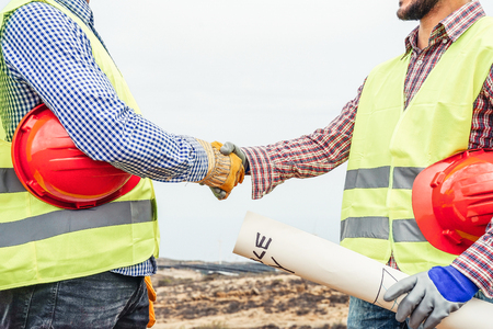 Builders shaking hands making an agreement on costruction site - Workers reaching a deal on renewable energy project on the working site - Building, dealing, engineer industrial concept