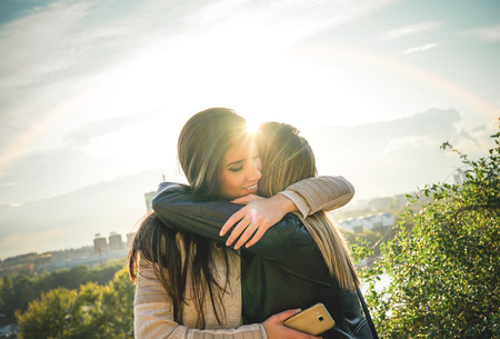 Happy meeting of two friends hugging at sunset outdoor - Pleasant moment of young sisters embracing in the wilderness as the sun shines upon them - Vignette editing Фото со стока