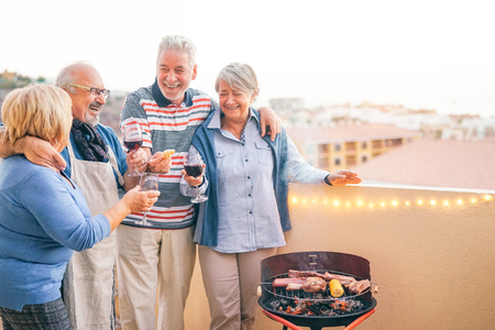 Happy senior friends having fun drinking red wine at barbecue dinner in terrace - Mature people dining and laughing together on rooftop - Friendship and elderly lifestyle concept Stock fotó