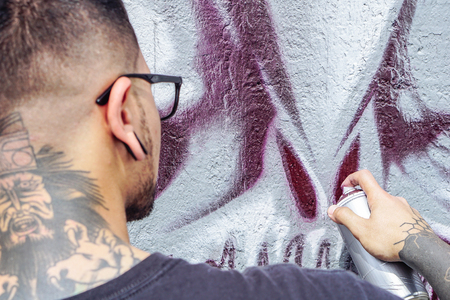 Street graffiti artist painting with a color spray can a dark monster skull graffiti on the wall in the city outdoor - Close up hand paints - Urban, lifestyle contemporary street art concept