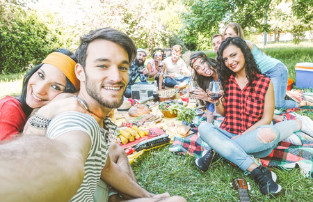 Group of friends taking a selfie in the park on a sunny day - Happy people having a picnic eating and drinking wine while taking photo with a mobile phone - Friendship, lifestyle, recreation concept
