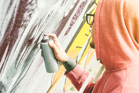 Street artist painting graffiti with color spray his art on the wall - Young man writing and drawing murales on the street - Urban lifestyle and contemporary art concept Stock Photo