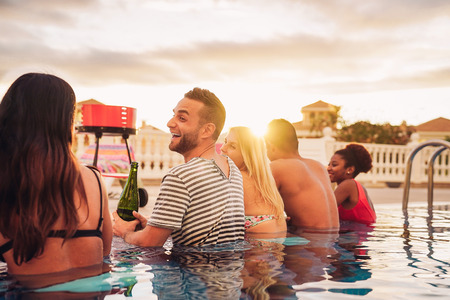 Happy friends making a pool party drinking champagne in the poolside - Young people in swimsuits having fun at barbecue dinner in luxury tropical resort at sunset - Youth holidays lifestyle concept