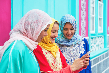 Happy muslim women watching on mobile smart phone in the college - Arabian young girls having fun with new technologies trends - Millennials, generation z and technology concept