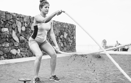 Fit woman training with battle rope outdoor - Female athlete doing arms exercises on the beach  - Body building and sport lifestyle concept - Black and white edit