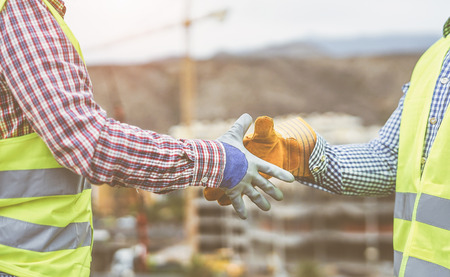 Close up builders hands making a deal - Workers on construction site reaching an agreement - Building, dealing, enginner industrial concept Reklamní fotografie