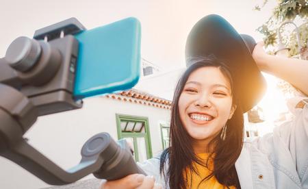 Asiatische Frau, die Videos mit Smartphone-Gimbal im Freien macht - Fröhliches asiatisches Mädchen, das Spaß mit neuen Technologietrends für soziale Medien hat - Millennials, Generation Z, Technologie- und Jugend-Lifestyle-Konzept