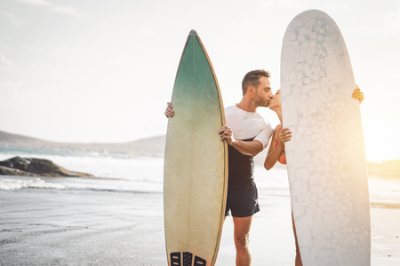 Happy couple of surfer kissing before to go to surf - Sporty people having a tender moment on the beach at sunset - Concept of sport lifestyle, extreme, love and relationship